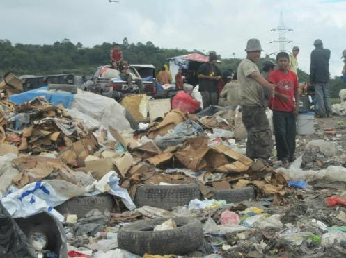 You can see one of the boys who lives at the dump and jumps into the back of the trucks searching for garbage.